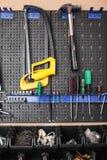 Закройте вверх по стойке с разнообразием инструментов в изолированной мастерской Стоковое Изображение