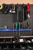 Закройте вверх по стойке с разнообразием современных инструментов в изолированной мастерской Стоковые Изображения RF