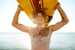 Закройте вверх по стороне красивого парня с surfboard на голове Стоковая Фотография RF