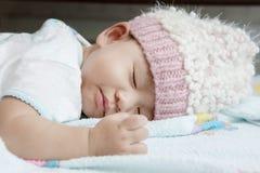 Закройте вверх по стороне младенца спать на клобуке шерстей кровати одежд нося стоковые фото