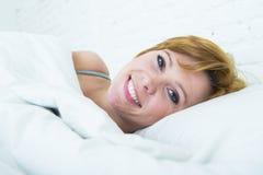 Закройте вверх по стороне молодой привлекательной женщины при красные волосы лежа в смотреть кровати дома усмехаясь счастливый зд Стоковое Изображение