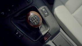 Закройте вверх по съемке высокого угла видео- ручной ручки шестерни автомобиля с коробкой передач в расплывчатой предпосылке видеоматериал