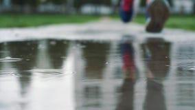 Закройте вверх по съемке в различной скорости ног бегуна в тапках Женские спорт укомплектовывают личным составом jogging outdoors