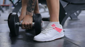Закройте вверх по съемке гантелей атлетической молодой женщины поднимаясь на спортзале сток-видео