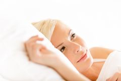 Закройте вверх по съемке лежать в женщине кровати стоковые фото