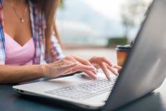 Закройте вверх по съемке женских рук печатая на клавиатуре компьтер-книжки Молодая женщина изучая и работая в парке Стоковые Изображения