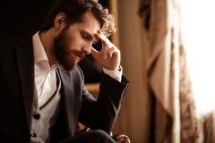 Закройте вверх по съемке задумчивого бородатого человека в элегантном официально костюме, обдумайте о что-то, имейте некоторые пр стоковые изображения