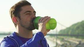 Закройте вверх по съемке красивой питьевой воды молодого человека после разработки акции видеоматериалы