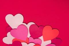 Закройте вверх по съемке красочных бумажных сердец на красной бумажной предпосылке Стоковые Фото