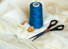 Закройте вверх по съемке ножниц и шить потоков на бежевой сатинировке стоковые фотографии rf