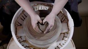 Закройте вверх по съемке рук ` s женщины, попыток студента для того чтобы создать глиняный горшок в мастерской для курсов гончарн сток-видео