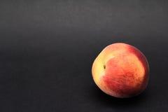 Закройте вверх по съемке свежего персика на черной предпосылке Стоковое Фото