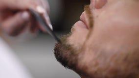 Закройте вверх по съемке стороны ` s человека, к которой заботить для бороды сделан, волосы на стороне аккуратно уравновешивает и акции видеоматериалы