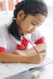 Закройте вверх по съемке Potriat азиатской маленькой девочки сидя и делая hom стоковые изображения rf