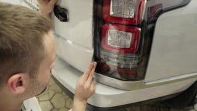 Закройте вверх по съемке unstick рук ` s человека фильм с автомобилем белого cowl дорогим сток-видео