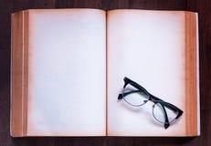 Закройте вверх по тетради и eyeglasses на деревянной предпосылке Стоковые Фотографии RF