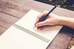 Закройте вверх по тетради сочинительства женщины руки с карандашем на деревянной таблице Стоковые Изображения