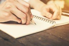 Закройте вверх по тетради сочинительства женщины руки с карандашем на деревянной таблице Стоковое Изображение RF