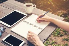 Закройте вверх по тетради сочинительства женщины руки с карандашем на деревянной таблице Стоковое фото RF