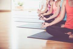 Закройте вверх по усаженным рукам группы йоги делающ руку Mudra и meditat Стоковые Изображения