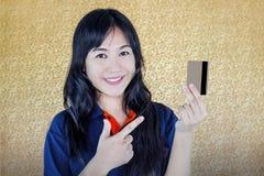 Закройте вверх по усмехаясь азиатским женщинам представляя назад дебита или кредита Стоковые Изображения RF