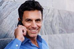 Закройте вверх по усмехаясь бизнесмену говоря на мобильном телефоне Стоковая Фотография