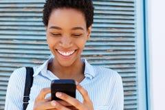 Закройте вверх по усмехаясь молодой африканской женщине держа мобильный телефон Стоковое Фото
