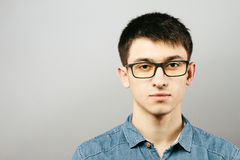 Закройте вверх по усмехаясь Eyeglasses молодого бизнесмена нося, смотря камеру против серой предпосылки стены с космосом экземпля Стоковые Изображения