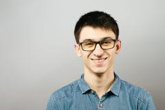 Закройте вверх по усмехаясь Eyeglasses молодого бизнесмена нося, смотря камеру против серой предпосылки стены с космосом экземпля Стоковое Изображение RF