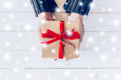 Закройте вверх по удерживанию женщины руки и подарочной коробке персоны на деревянных wi таблицы Стоковое Изображение RF