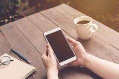 Закройте вверх по удерживанию женщины руки и телефон использования на деревянной таблице с v Стоковое фото RF