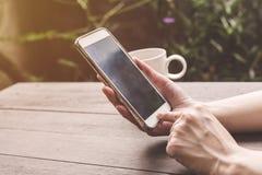 Закройте вверх по удерживанию женщины руки и телефон использования на деревянной таблице с v Стоковая Фотография RF