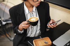 Закройте вверх по фото Афро-американской девушки сидя на таблице кафа с мобильным телефоном и чашкой кофе в руках Дама Стоковые Фото