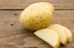 Закройте вверх по фото всех свежих картошки и кусков на деревянной таблице Стоковые Изображения RF