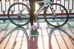 Закройте вверх по фото женских ног велосипедиста и велосипед дороги катит внутри холодный солнечный день осени уклад жизни принци Стоковые Изображения