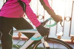 Закройте вверх по фото женских рук велосипедиста в перчатках на Handlebar велосипеда дороги в холодном солнечном дне осени Здоров Стоковое фото RF