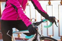 Закройте вверх по фото женских рук велосипедиста в перчатках на Handlebar велосипеда дороги в холодном солнечном дне осени Здоров Стоковые Фото