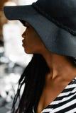 Закройте вверх по фото привлекательной американской девушки Женский смотрящ кто-то Модель в черной шляпе Стоковые Изображения RF
