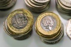 Закройте вверх по фото фокуса новой монетки фунта Великобритании, среди других великобританских монеток Стоковые Фото