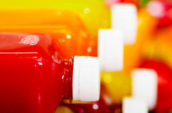 Закройте вверх по цветам верхней части бутылок сока лежа вниз штабелированным, красивым и здоровой концепции Стоковая Фотография RF