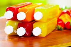 Закройте вверх по цветам верхней части бутылок сока лежа вниз штабелированным, красивым и здоровой концепции Стоковое Изображение RF