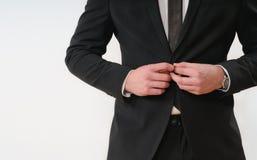 Закройте вверх по части кнопки стороны тела бизнесмена вверх по его черному костюму Стоковое фото RF