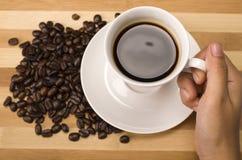 Закройте вверх по чашке кофе в руке стоковое изображение rf