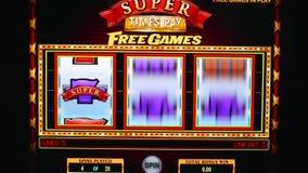 Закройте вверх по человеку играя торговый автомат на экране компьютера акции видеоматериалы