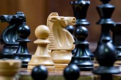 Закройте вверх по черно-белым figurines шахмат на шахматной доске Стоковое Изображение