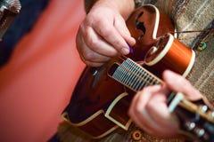 Закройте вверх по человеку рук старшему играя мандолину Стоковое фото RF