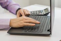 Закройте вверх по человеку multitasking рук используя wifi компьтер-книжки соединяясь Стоковое фото RF