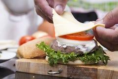 Закройте вверх по шеф-повару кладя кусок сыра на плюшку гамбургера Стоковое Фото