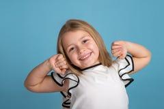 Закройте вверх по эмоциональному портрету молодой белокурой усмехаясь девушки нося белое blous с черными прокладками на голубой п стоковое фото rf