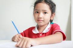 Закройте вверх по potrait съемки азиатской маленькой девочки делая домашнюю работу стоковые фотографии rf